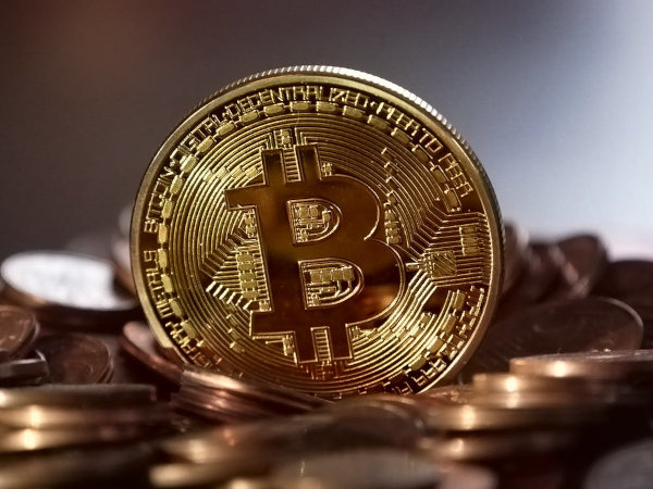 A photo of a coin with the Bitcoin sign.