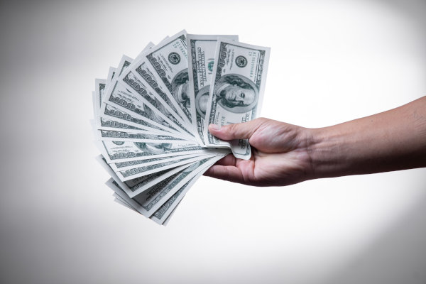 A person holding cash.